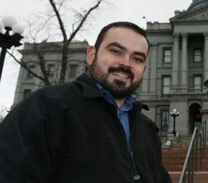 In this Tuesday, Dec. 23, 2014 photo, Edgar Antillon, one of the organizers of an effort to have a ballot measure placed before voters in the 2016 November election to allow marijuana users to carry concealed firearms, stands outside the State Capitol, in downtown Denver. The measure would change state law to prevent sheriffs from using marijuana use as a reason to deny a concealed carry permit to an applicant. (AP Photo/David Zalubowski)